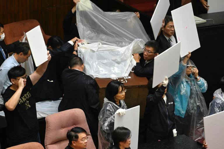 DPP legislators donned plastic raincoats and used cardboard shields to protect themselves from the water balloons