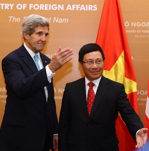 U.S. Secretary of State John Kerry, left, poses with Vietnamese Foreign Minister Pham Binh Minh during a talk in Hanoi Monday, Dec. 16, 2013. Secretary of State Kerry is in Vietnam pressing the communist country on democratic and economic reforms and offering U.S. assistance to protect its maritime borders. (AP Photo/Hoang Dinh Nam, Pool)