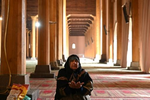 A woman prays in the main mosque in Srinagar after it opened for the first time in nearly five  months