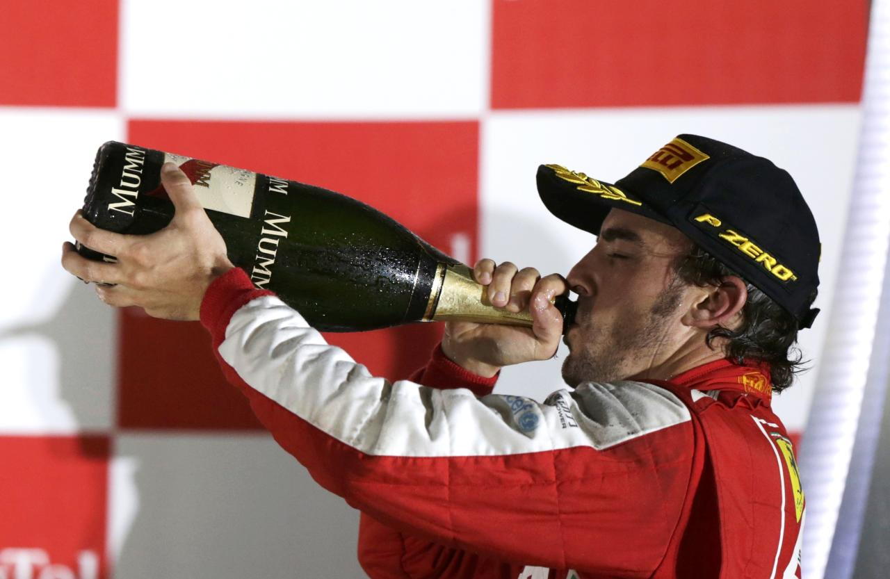 Ferrari Formula One driver Fernando Alonso of Spain drinks champagne on the podium after the Singapore F1 Grand Prix at the Marina Bay street circuit in Singapore September 22, 2013. REUTERS/Pablo Sanchez (SINGAPORE - Tags: SPORT MOTORSPORT F1)