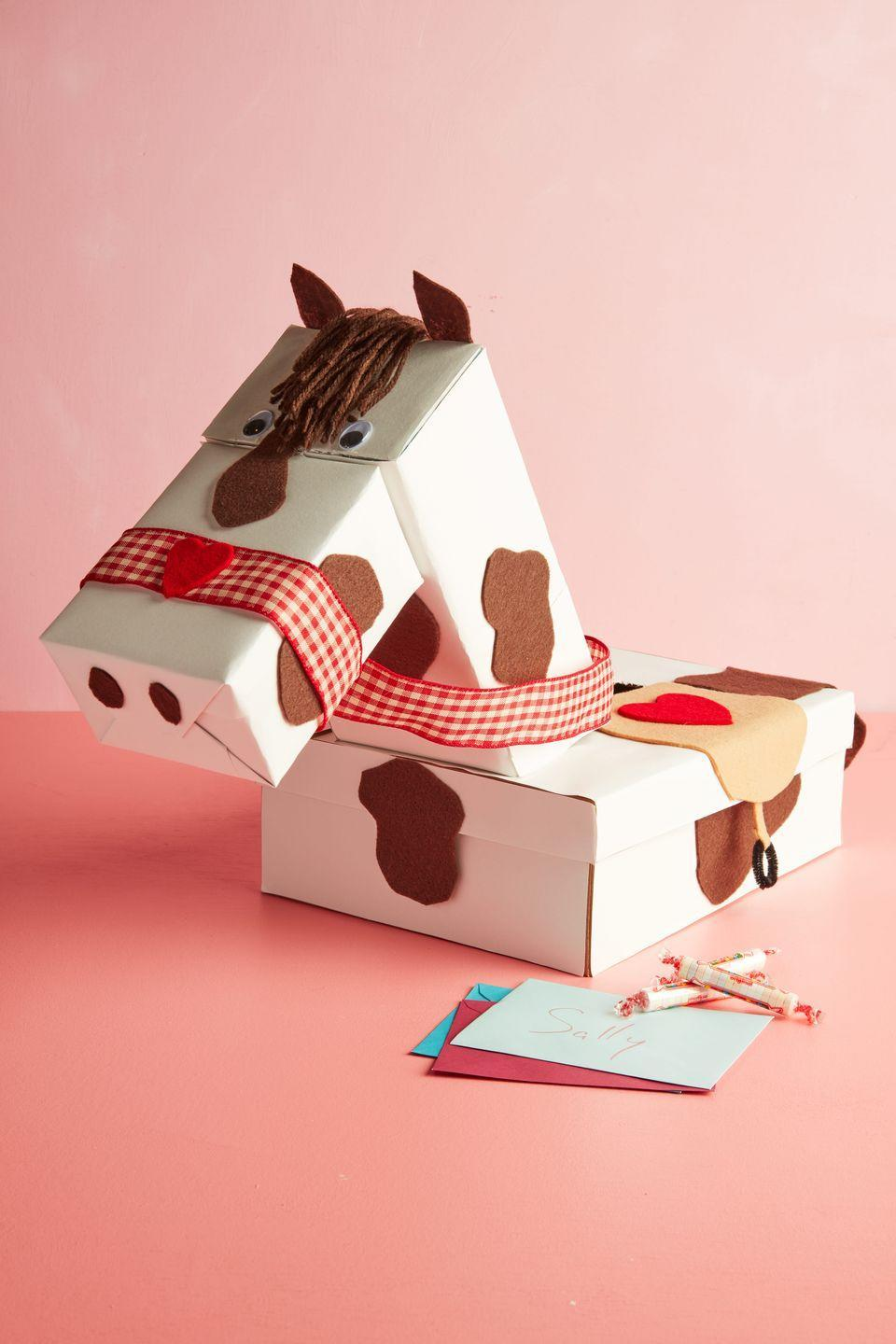 "<p>The ideal project for the horse loving kiddo in your house. Neigh!<strong><br></strong></p><p><strong>To make:</strong> Wrap a rectangular <a href=""https://www.amazon.com/Factory-Direct-Craft-Decorate-Rectangle/dp/B00CMB8TCQ/ref=sr_1_44"" rel=""nofollow noopener"" target=""_blank"" data-ylk=""slk:papier-mâché"" class=""link rapid-noclick-resp"">papier-mâché</a><a href=""https://www.amazon.com/Factory-Direct-Craft-Decorate-Rectangle/dp/B00CMB8TCQ/ref=sr_1_44"" rel=""nofollow noopener"" target=""_blank"" data-ylk=""slk:box"" class=""link rapid-noclick-resp""> box</a> in white craft paper. Cut a slit in the top. Cut one end a shoe box at an angle to create the neck; wrap in white craft paper. Cut a second shoe box to create the horse's muzzle; wrap in white craft paper. Attach parts together with hot glue. Cut spots, ears, saddle, and decorative details from dark brown and light brown felt. Cut hearts from red felt. Attach to the horse with a glue stick. Attach a thin strip of felt to the bottom of the saddle. Make two small loops from black pipe cleaners and attach to the bottom of the strip to create stirrups. Wrap red gingham ribbon around the nose and neck to create the reins and noseband; attach with glue stick. Glue googly eyes to the face. Cut short lengths of <a href=""https://www.amazon.com/Bernat-Yarn-Small-Ball-Brown/dp/B0100JA3KW/ref=sr_1_8"" rel=""nofollow noopener"" target=""_blank"" data-ylk=""slk:brown yarn"" class=""link rapid-noclick-resp"">brown yarn</a> and attach between the ears to create the mane.</p><p><a class=""link rapid-noclick-resp"" href=""https://www.amazon.com/flic-flac-inches-Assorted-Fabric-Patchwork/dp/B01GCRXBVE/ref=sr_1_2_sspa?tag=syn-yahoo-20&ascsubtag=%5Bartid%7C10050.g.25844424%5Bsrc%7Cyahoo-us"" rel=""nofollow noopener"" target=""_blank"" data-ylk=""slk:SHOP FELT"">SHOP FELT</a></p>"