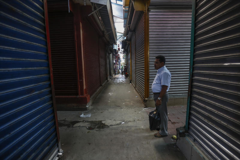 In this Sept 7, 2018 photo, a man walks in the empty and shuttered halls of the Oriental Market during a 24 hour national strike, in Managua, Nicaragua. In June, the country's economic activity was down 12.1 percent compared to a year earlier, according to the central bank. (AP Photo/Alfredo Zuniga)