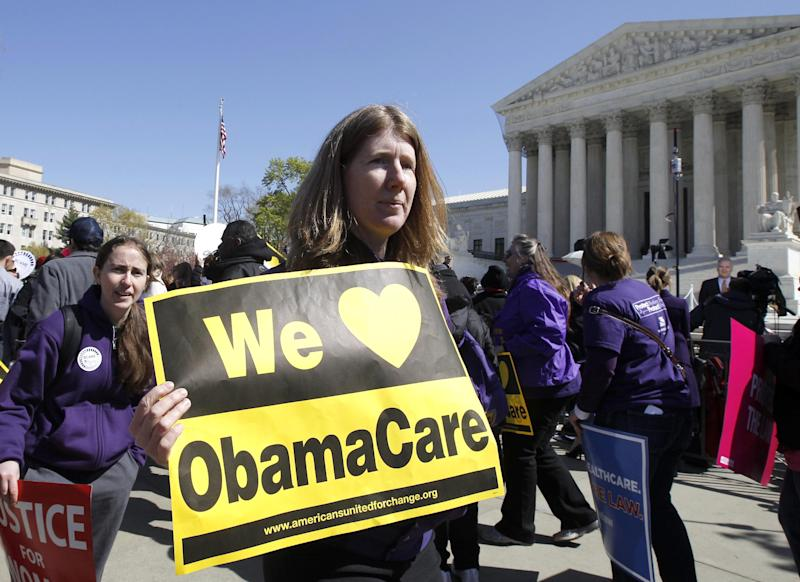 "Holding a sign saying ""We Love ObamaCare"" supporters of health care reform rally in front of the Supreme Court in Washington, Tuesday, March 27, 2012, as the court continued hearing arguments on the health care law signed by President Barack Obama. Go ahead, call it Obamacare. Obama's re-election campaign has lifted an unofficial ban on using the opposition's derisive term for his health care law. Democratic activists have been chanting, ""We love Obamacare,"" in front of the Supreme Court. And the campaign is selling T-shirts and bumper stickers that proclaim: ""I like Obamacare."" (AP Photo/Charles Dharapak)"