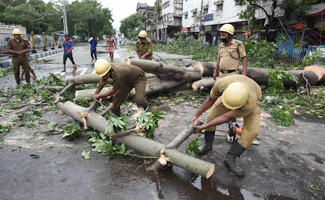 Disaster Management teams clear the streets of uprooted trees at Esplanade after Cyclone Amphan in Kolkata. (Photo by Samir Jana/Hindustan Times via Getty Images)