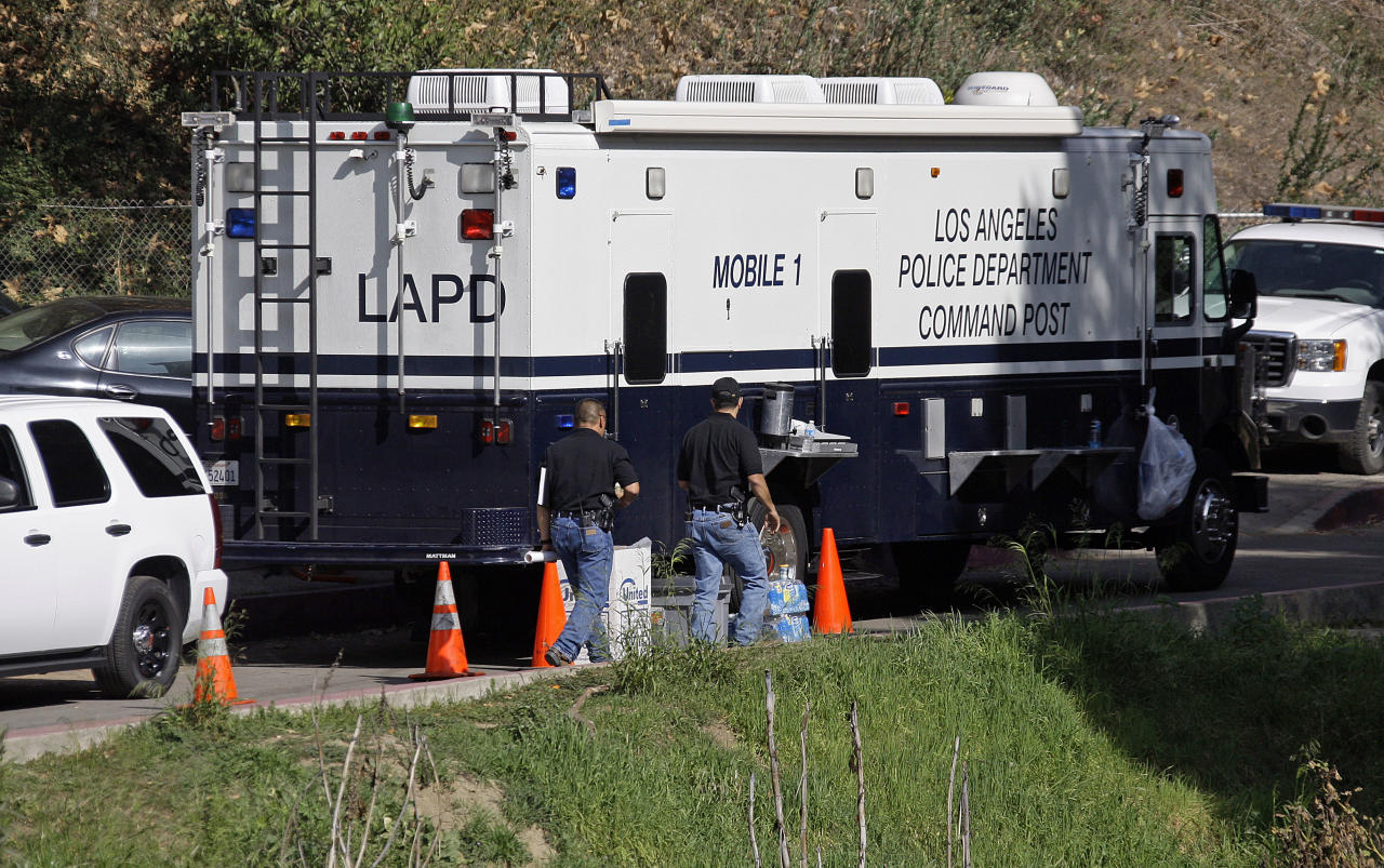 Los Angeles Police investigators are seen at a mobile command post as search operations for more human body parts near an end in Bronson Canyon in the Griffith Park area of Los Angeles Thursday, Jan. 9, 2012. Police worked to identity a man whose body was found in parts over the past two days — first a head on Tuesday, then two hands and two feet on Wednesday. On Thursday, some 100 police officers and Police Academy recruits searched seven acres of brush in the Bronson Canyon wilderness park in Hollywood to see if they could find more body parts. (AP Photo/Reed Saxon)