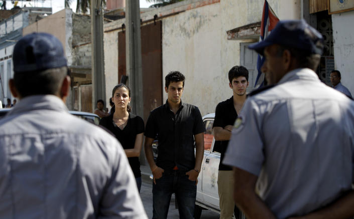 Police block the courthouse, keeping the children of late Cuban dissident Oswaldo Paya from attending the trial of Spanish citizen Angel Carromero, who is on trial for the death of their father, in Bayamo, Cuba, Friday, Oct. 5, 2012. Authorities accused Carromero of speeding and charged him with the equivalent of vehicular manslaughter, and prosecutors asked the court for a seven-year sentence. The car crash killed Paya and another dissident, Harold Cepero on July 22. A panel of judges will now consider the evidence and issue a ruling at an unspecified future date. At left is Rosa Maria Paya, at center is Oswaldo Paya and at right Reinaldo Paya. (AP Photo/Franklin Reyes)
