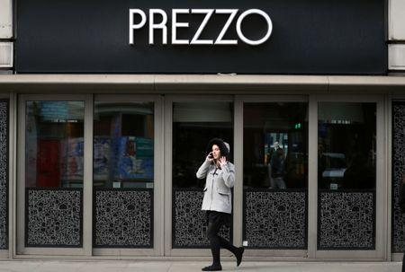 FILE PHOTO: A woman walks past a Prezzo restaurant in London
