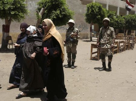 An elderly women is helped after voting during Egyptian presidential election in Ashmoon city