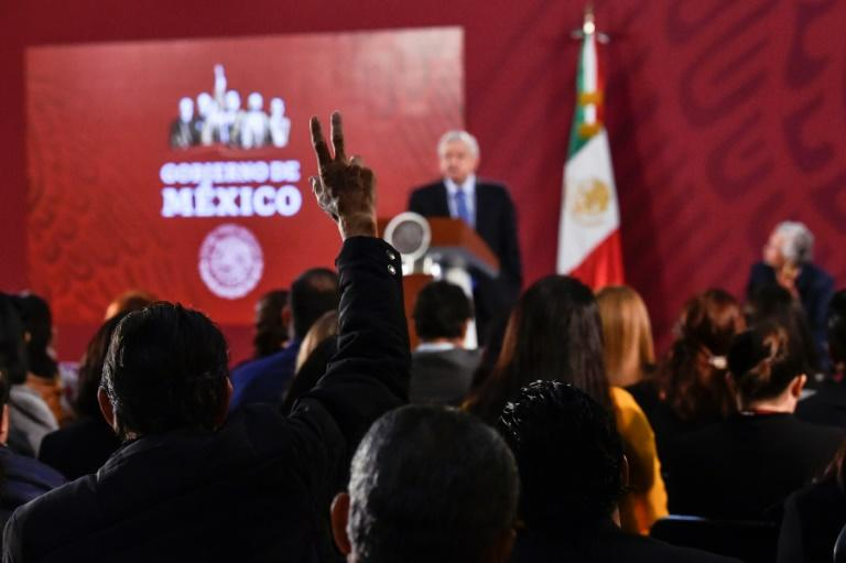 A reporter raises his hand to ask a question during Mexican President Andres Manuel Lopez Obrador's daily morning press conference at the National Palace in Mexico City on November 21, 2019