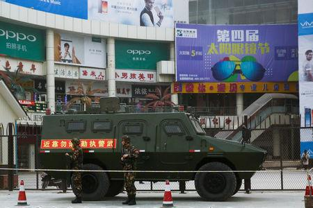 Security personel stand in front of an armoured vehicle in Kashgar