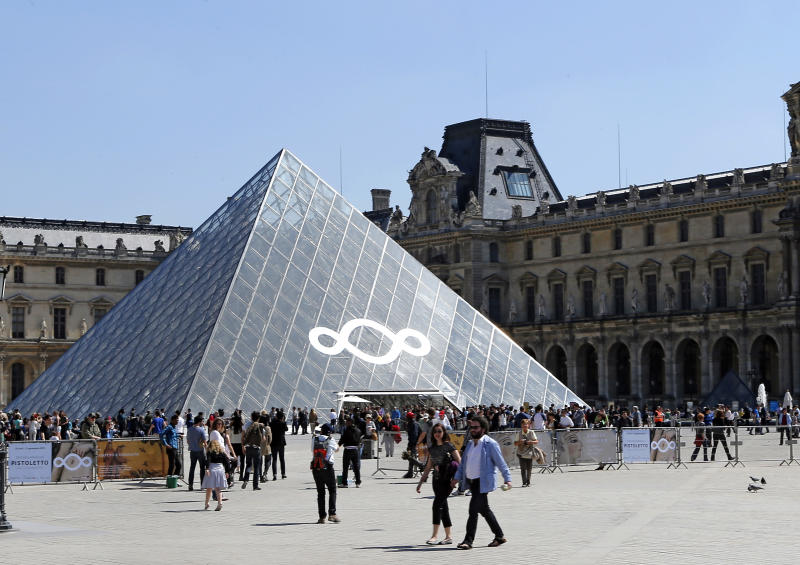Italian artist Michelangelo Pistoletto's art work decorates the Louvre museum's iconic glass pyramid, in Paris, Wednesday, April 24, 2013. Michelangelo Pistoletto, one of the world's leading conceptual artists, covered one panel of the pyramid with a huge three-looped infinity sign made of mirrors Wednesday. It's an artistic gesture aimed to show politicians and society the follies of excess that led to the current financial crisis.  (AP Photo/Jacques Brinon)
