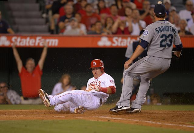 Los Angeles Angels' Mike Trout, left, scores on a wild pitch as Seattle Mariners starting pitcher Joe Saunders takes a late throw during the sixth inning of their baseball game, Wednesday, June 19, 2013, in Anaheim, Calif. (AP Photo/Mark J. Terrill)
