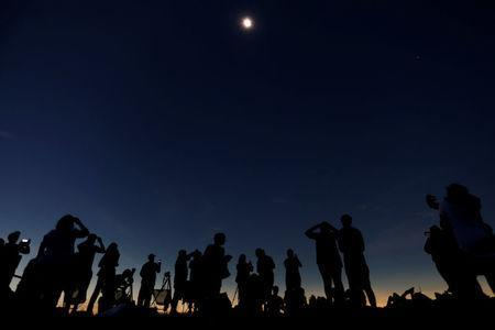 """People watch the total solar eclipse from Clingmans Dome, which at 6,643 feet (2,025m) is the highest point in the Great Smoky Mountains National Park, Tennessee, U.S. August 21, 2017. Location coordinates for this image are 35º33'24"""" N, 83º29'46"""" W. REUTERS/Jonathan Ernst"""
