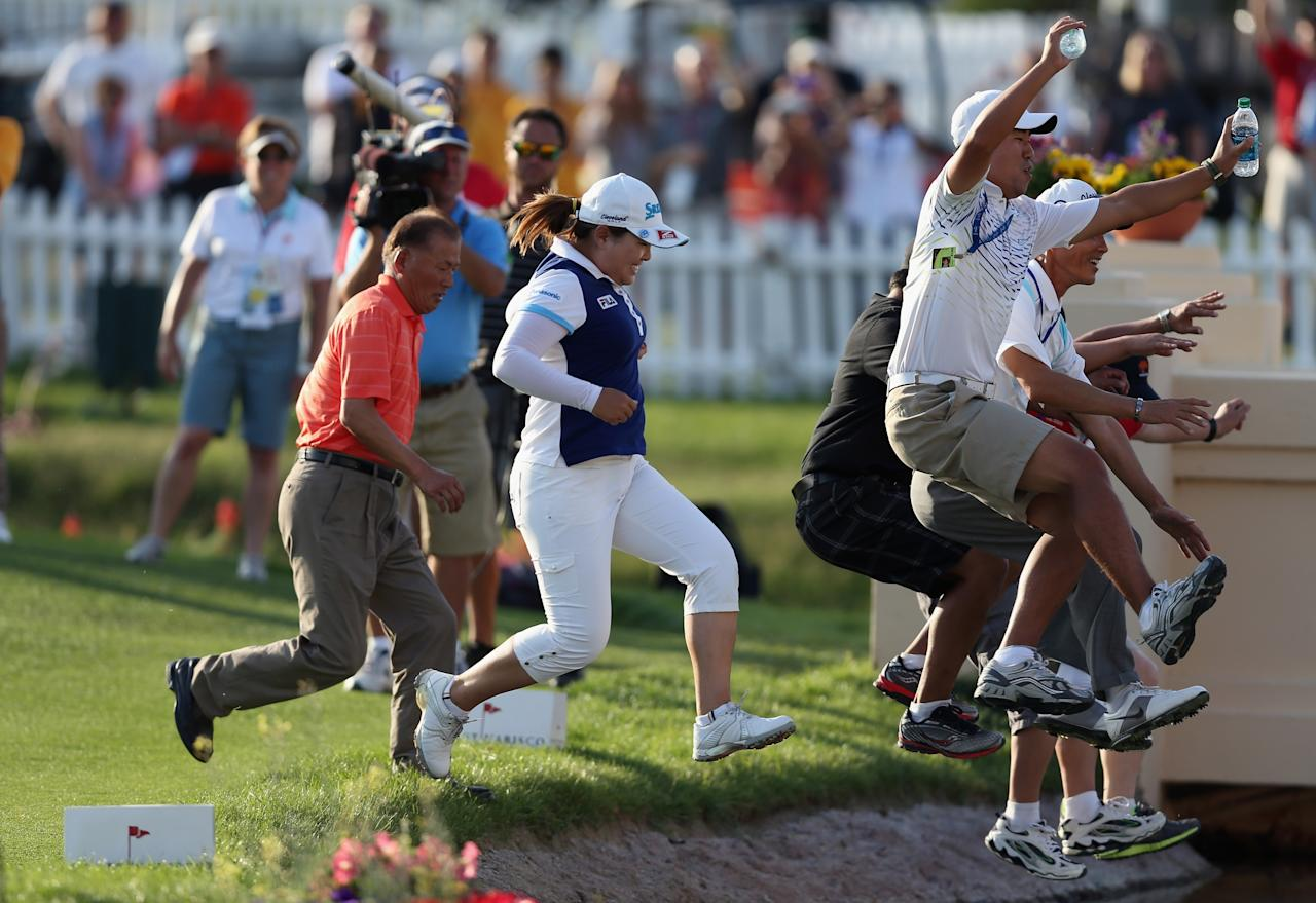 RANCHO MIRAGE, CA - APRIL 07:  Inbee Park of South Korea celebrates by jumping into Poppie's Pond along with fiance Gi Hyub Nam (R) after winning the Kraft Nabisco Championship at Mission Hills Country Club on April 7, 2013 in Rancho Mirage, California.  (Photo by Jeff Gross/Getty Images)