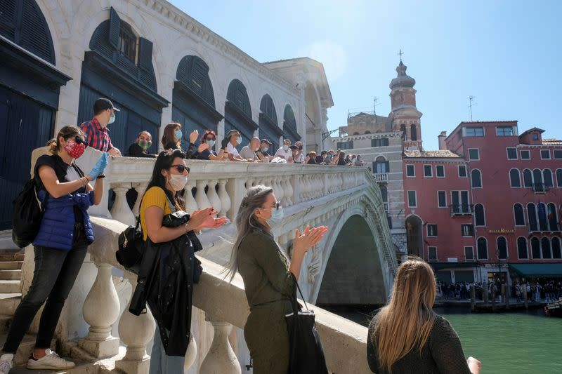 A rally organised by small business owners stops by the Rialto bridge to commemorate the health care workers as Italy begins a staged end to a nationwide lockdown due to a spread of the coronavirus disease (COVID-19), in Venice