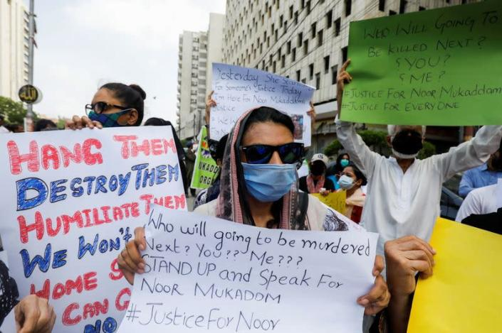 People carry signs to condemn the violence against women and girls during a protest in Karachi