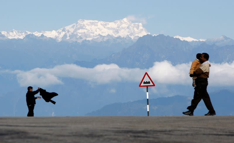 FILE PHOTO: A man with a child walks in front of the Gankar Punsun glacier at Dochula