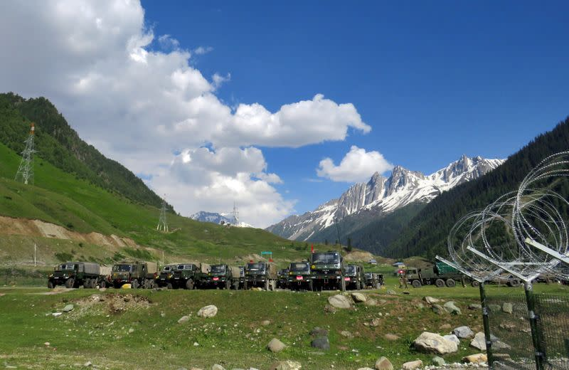 Indian army soldiers walk past their parked trucks at a makeshift transit camp before heading to Ladakh, near Baltal