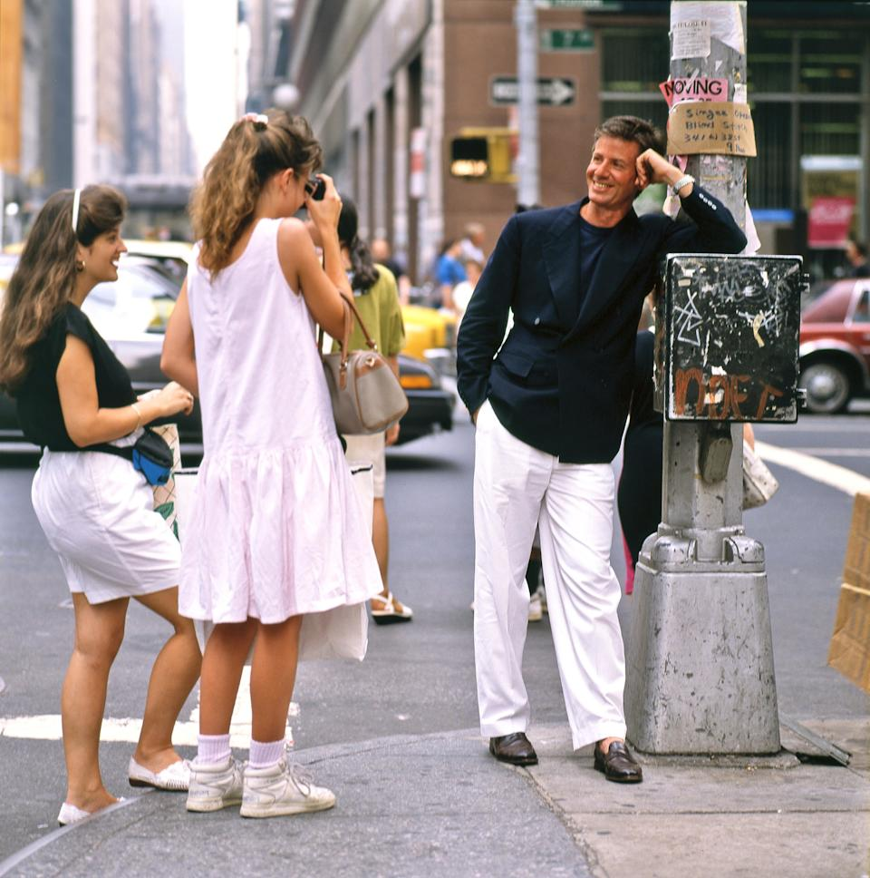 Calvin Klein standing on a corner of Seventh Avenue in Manhattan in 1989 while two young fans photograph him.