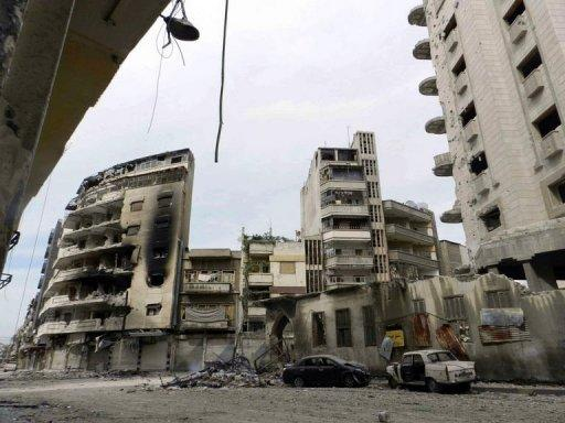 A handout picture released by Shaam News Network shows the destruction of buildings and vehicles in Homs on April 14