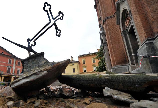 The toppled cross of a church lies amid debris in Crevalcore, northern Italy, Sunday, May 20. 2012. A magnitude-6 earthquake shook northern Italy early Sunday at 4:04 a.m. between Modena and Mantova, about 35 kilometers (22 miles) north of Bologna at a relatively shallow depth of 10 kilometers (6 miles). (AP Photo/Marco Vasini)
