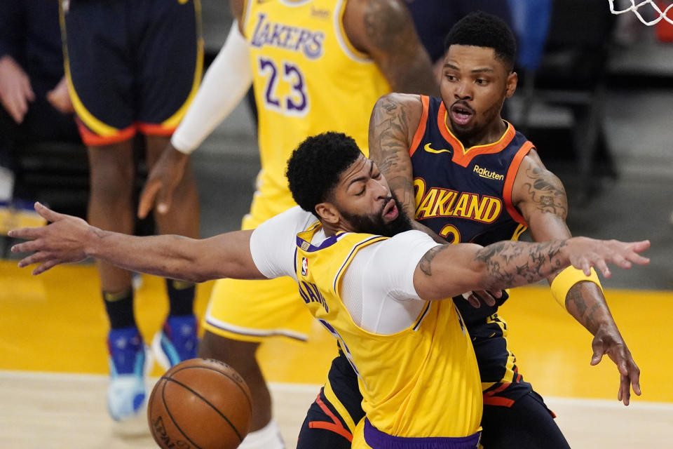Golden State Warriors forward Kent Bazemore, right, passes the ball past Los Angeles Lakers forward Anthony Davis during the first half of an NBA basketball Western Conference Play-In game Wednesday, May 19, 2021, in Los Angeles. (AP Photo/Mark J. Terrill)