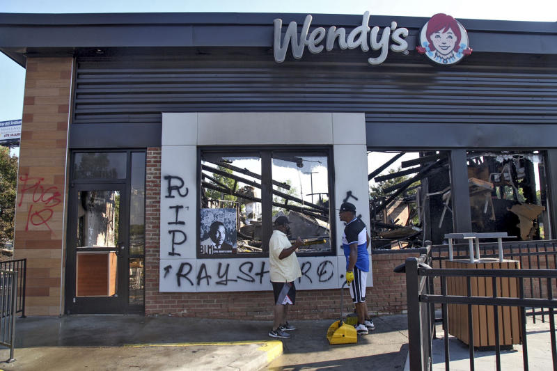 Renault Verona, right, and other area residents clean up the site Sunday, June 14, 2020 where protestors on Saturday set fire to the Atlanta Wendy's where Rayshard Brooks, a 27-year-old Black man, was shot and killed by Atlanta police Friday evening during a struggle in a Wendy's drive-thru line. (Steve Schaefer/Atlanta Journal-Constitution via AP)