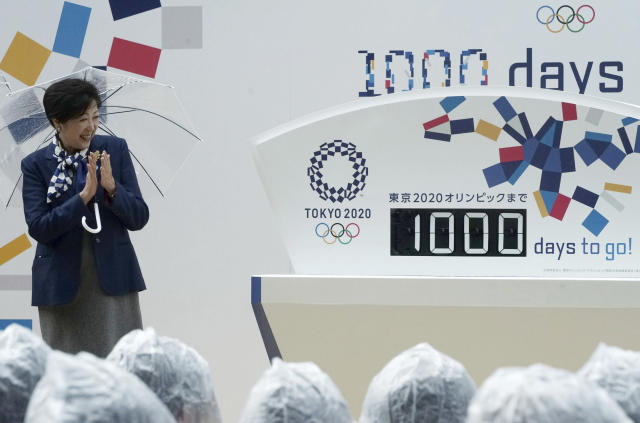 FILE - In this Oct. 28, 2017, file photo, Tokyo Gov. Yuriko Koike claps while looking at the day counter after it's unveiled during a Tokyo 2020 Olympics countdown event in Tokyo. Tokyo used its famous 1964 Olympics to show off a miraculous recovery from defeat in World War II. This time the Japanese capital will use the games to showcase a clean, safe, and innovative city with great shopping and nightlife. (AP Photo/Eugene Hoshiko, File)