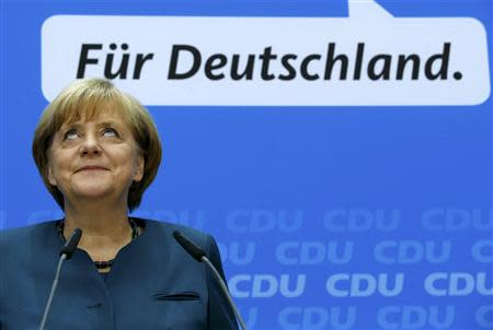 German Chancellor and leader of the Christian Democratic Union ( CDU) Angela Merkel, smiles during a news conference after a CDU party board meeting in Berlin September 23, 2013, the day after the general election. Merkel faces the daunting prospect of persuading her centre-left rivals to keep her in power after her conservatives notched up their best election result in more than two decades but fell short of an absolute majority. REUTERS/Fabrizio Bensch