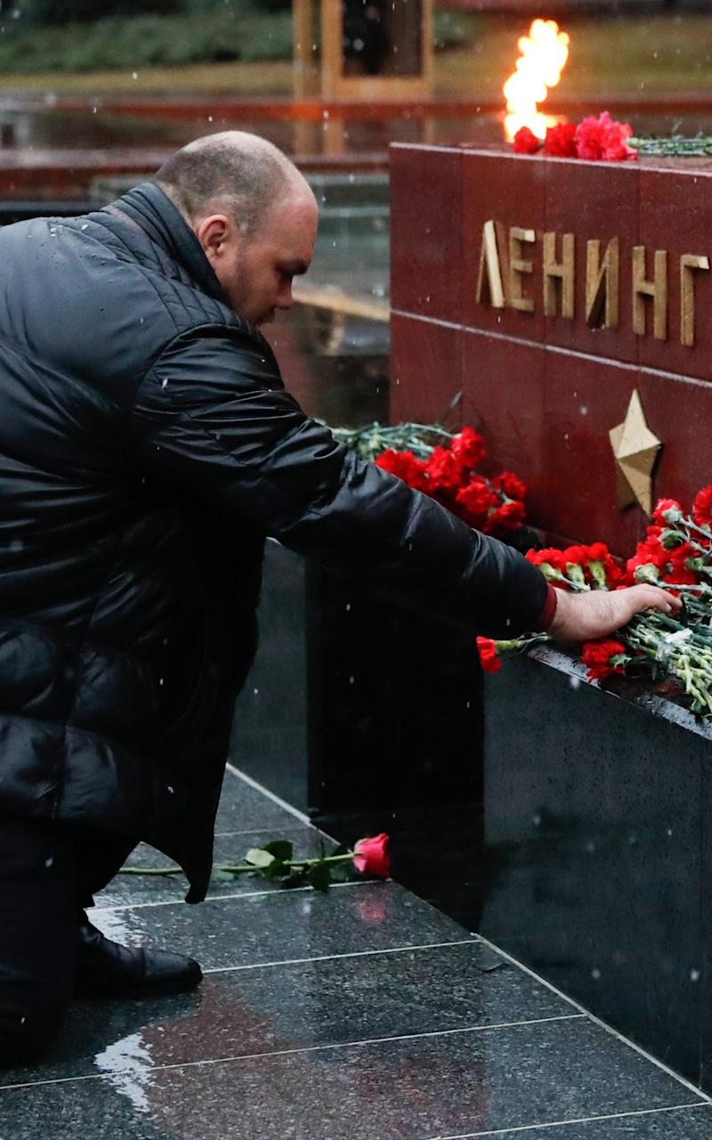 A man lays flowers at the Leningrad Hero City memorial by the Kremlin Wall in Moscow in memory of Monday's victims - Credit: TASS / Barcroft Images