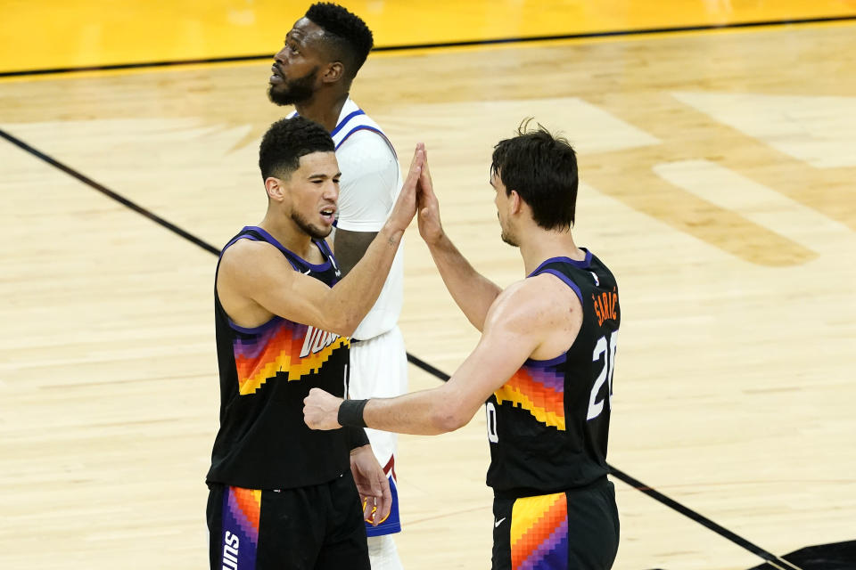 Phoenix Suns guard Devin Booker, left, high fives forward Dario Saric after a three pointer against the Denver Nuggets during the first half of Game 2 of an NBA basketball second-round playoff series, Wednesday, June 9, 2021, in Phoenix. (AP Photo/Matt York)