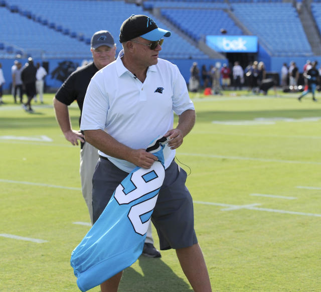 Carolina Panthers owner David Tepper carries Julius Peppers jersey as he walks to mid-field before a preseason NFL football game against the Miami Dolphins in Charlotte, N.C., Friday, Aug. 17, 2018. (AP Photo/Mike McCarn)