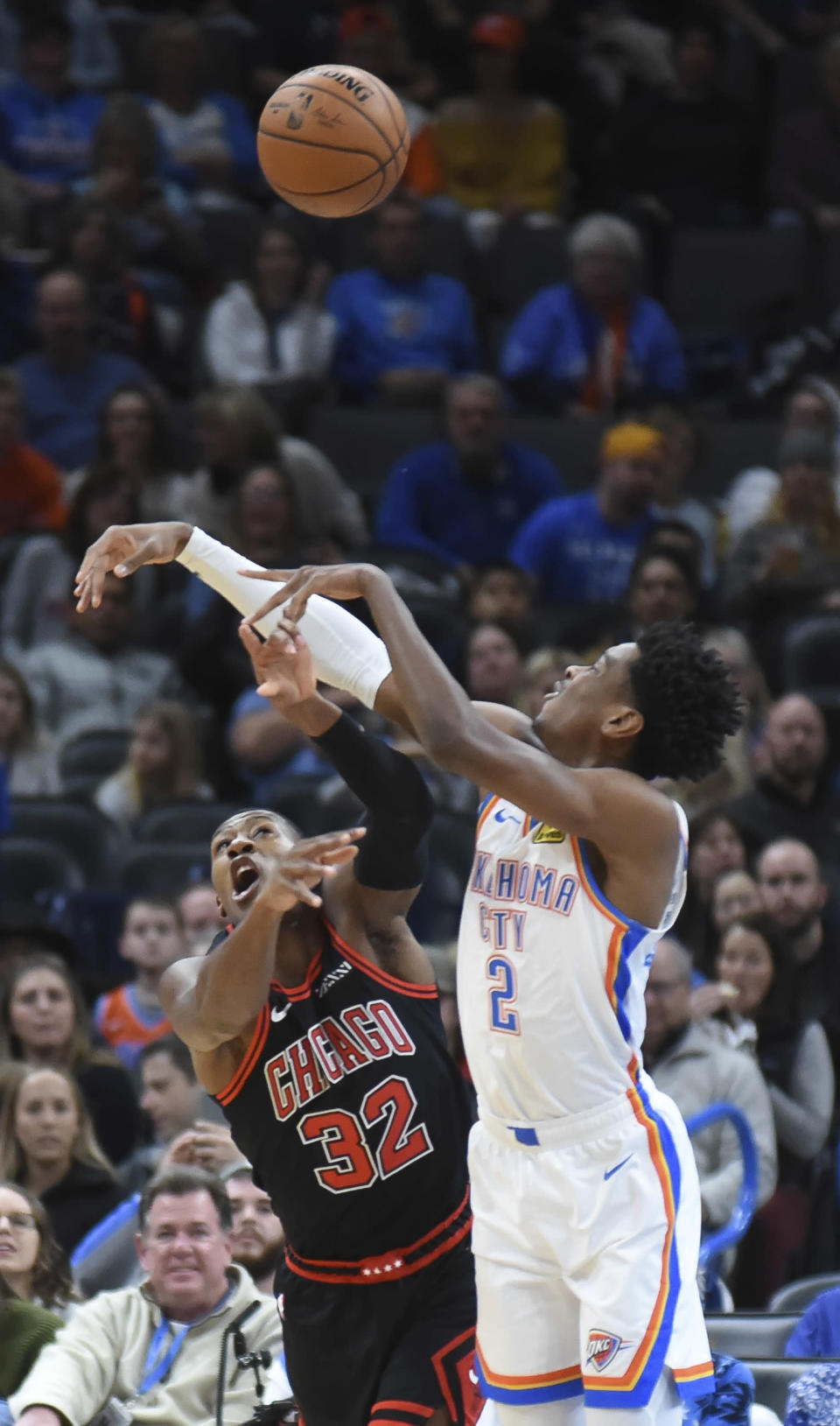 Chicago Bulls guard Kris Dunn (32) tries to block a shot by Oklahoma City Thunder guard Shia Gilgeous- Alexander (2) in the first half of an NBA basketball game, Monday, Dec. 16, 2019, in Oklahoma City. (AP Photo/Kyle Phillips)