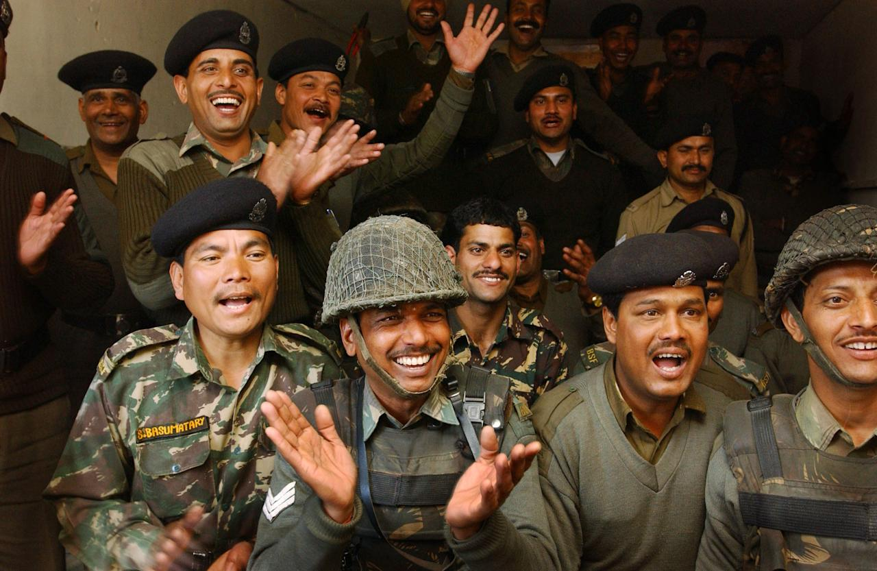 SRINAGAR, KASHMIR, INDIA - MARCH 13: Indian Border Security Force soldiers, who are part of the 98th battalion, celebrate as they watch the Indian cricket team play Pakistan in the first one-day international cricket match held in Karachi, Pakistan, March 13, 2004 at their camp in Srinagar, India. This is the first cricket tour held in Pakistan between the two nations in 14 years.  (Photo by Ami Vitale/Getty Images)