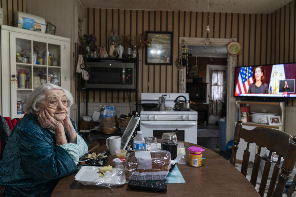 Rita Scanlon, 92, eats lunch delivered to her by Meals on Wheels of Rhode Island as she listens to Gov. Gina Raimondo's press conference urging residents to stay home for Thanksgiving amidst an increase in COVID hospitalizations, Wednesday, Nov. 25, 2020, in Central Falls, R.I. As more at-risk seniors find themselves unable to leave their homes during the pandemic, Meals on Wheels of Rhode Island has been delivering on average 4,000 meals per day up from their pre-pandemic average of 1,200. (AP Photo/David Goldman)