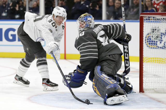 Vancouver Canucks forward Elias Pettersson (40) reaches for the puck as he closes in on St. Louis Blues goalie Jordan Binnington (50) in an NHL hockey All Star semifinal game Saturday, Jan. 25, 2020, in St. Louis. (AP Photo/Jeff Roberson)