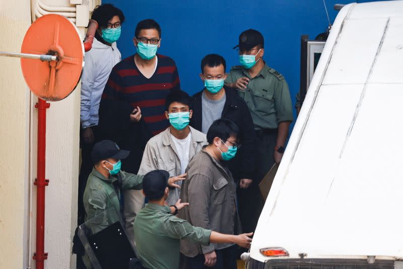Pro-democracy activists Sam Cheung, Lam Cheuk-ting, Raymond Chan Chi-chuen and Owen Chow walk to a prison van to head to court, over national security law charges, in Hong Kong
