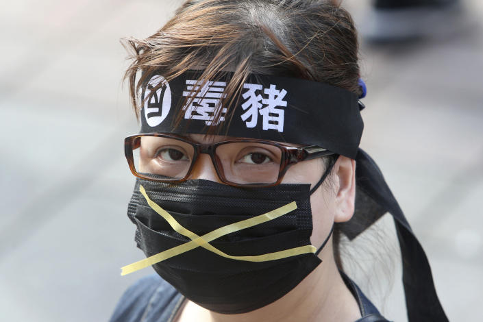 """A Taiwanese woman wears a headband with a slogan """"Anti-poisoned pork"""" during a protest in Taipei, Taiwan, Sunday, Nov. 22. 2020. Thousands of people marched in streets on Sunday demanding the reversal of a decision to allow U.S. pork imports into Taiwan, alleging food safety issues. (AP Photo/Chiang Ying-ying)"""