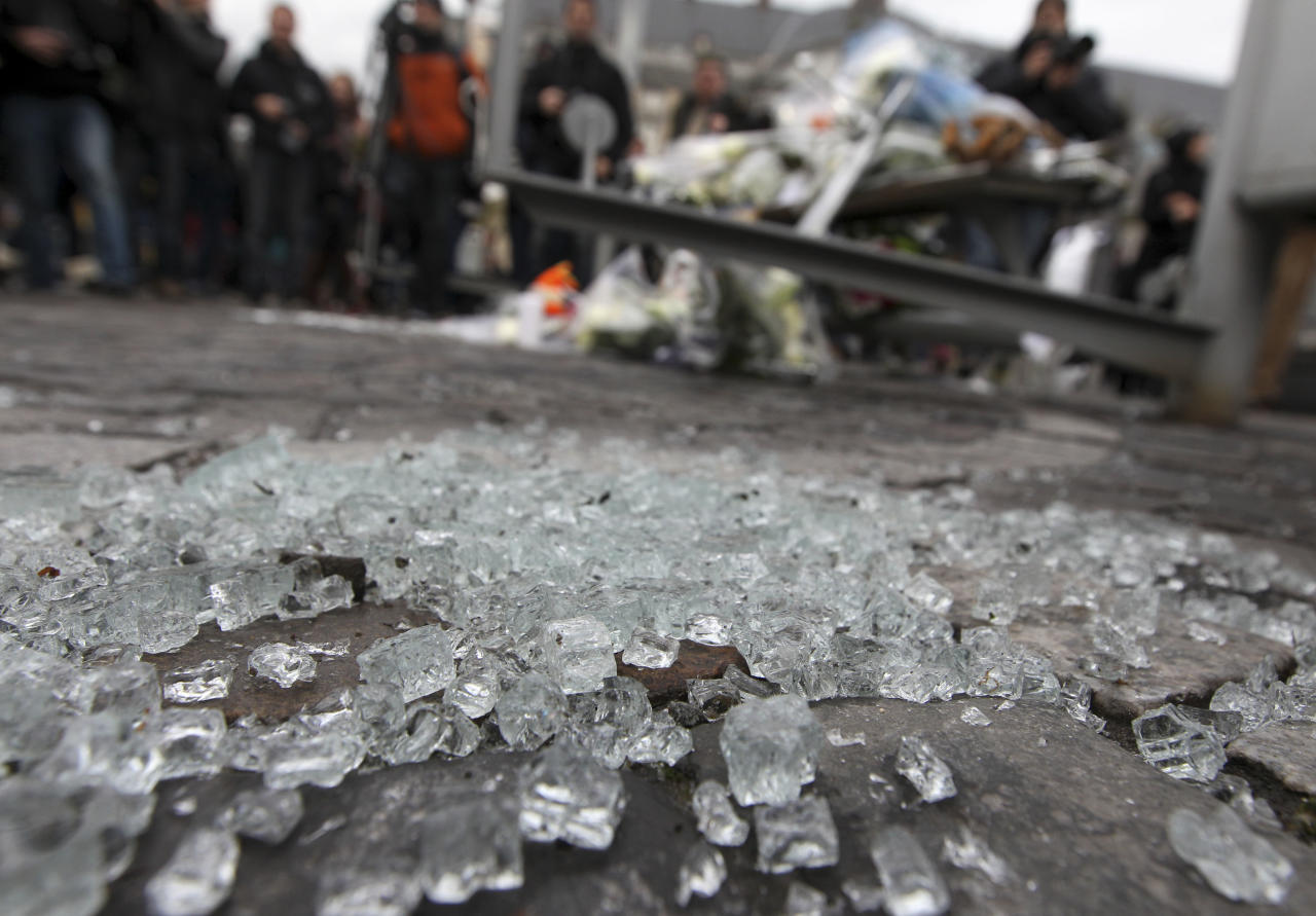 Shattered glass is seen at a bus stop at the scene of Tuesday's attack, in the city center of Liege, Belgium, Wednesday, Dec. 14, 2011. The body of a woman has been found in the garage of a grenade-lobbing gunman, bringing to four the number of people killed in an attack in the city of Liege, officials said Wednesday. (AP Photo/Yves Logghe)
