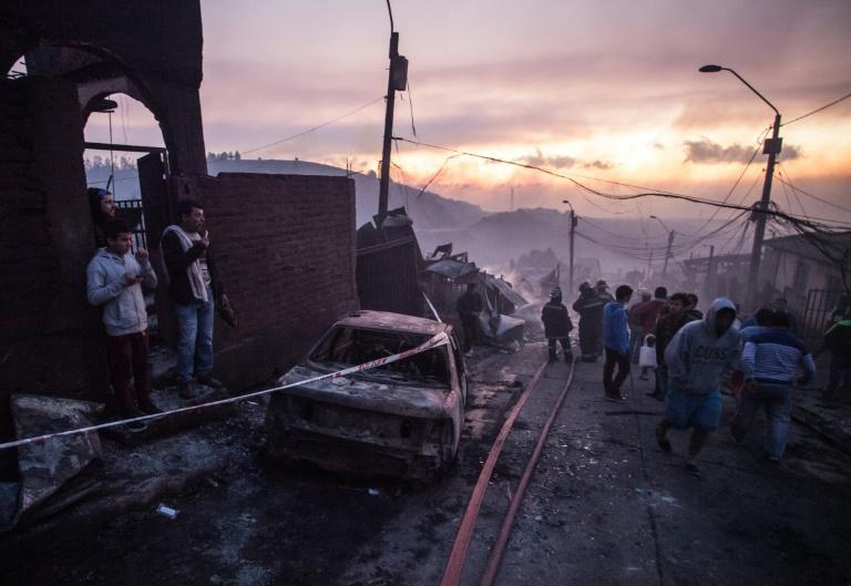 People work to extinguish the flames at a house in Valparaiso, Chile, where authorities have declared a red alert
