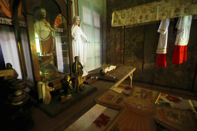 This Jan. 26, 2019 photo shows altar server vestments, right, and other religious images behind the altar chapel built by American priest Father Pius Hendricks in the village of Talustusan on Biliran Island in the central Philippines. Since December 2018, the small village has been rocked by controversy after about 20 boys and men accused the Catholic parish priest of years of alleged sexual abuse. (AP Photo/Bullit Marquez)