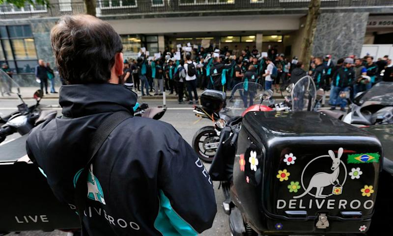 Deliveroo riders holding a protest over pay outside the company HQ in London