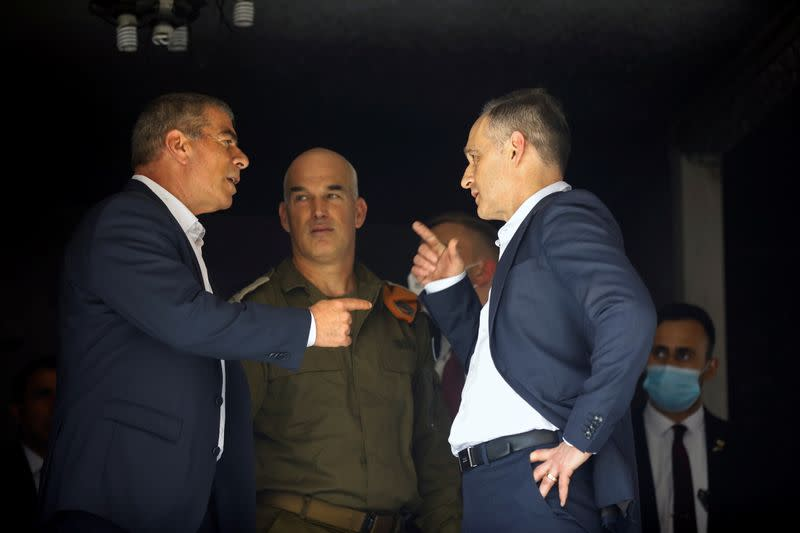 Israeli Foreign Minister Ashkenazi and his German counterpart Maas speak as they stand inside a damaged apartment during their visit to the site of a building hit by a rocket launched from the Gaza Strip last week, in Petah Tikva