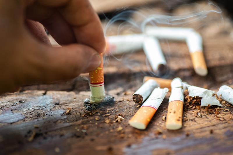 Hand putting out cigarette butt on table surrounded by other discarded cigarettes.