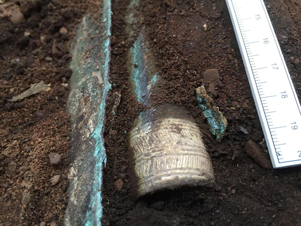 The gold-decorated socket of a Bronze Age spearhead emerges from the soil in Scotland. <cite>Guard Archaeology Ltd.</cite>