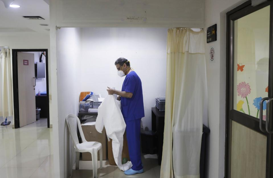 Dr. Kedar Toraskar, center, prepares his protective suit before entering the ICU ward of COVID-19 patients at the Mumbai Central Wockhardt Hospital in Mumbai, India, June 4, 2021. The recent coronavirus surge in India affected young people on a scale his team of critical care doctors hadn't previously seen. (AP Photo/Rajanish Kakade)