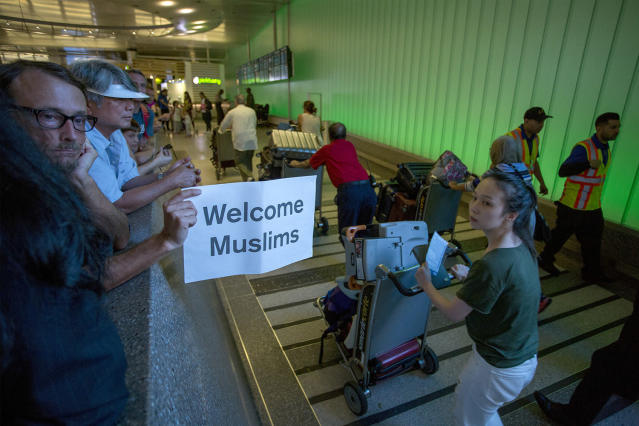 <p>John Wider carries a welcome sign near arriving international travelers on the first day of the the partial reinstatement of the Trump travel ban, temporarily barring travelers from six Muslim-majority nations from entering the U.S., at Los Angeles International Airport (LAX) on June 29, 2017 in Los Angeles, California. (David McNew/Getty Images) </p>