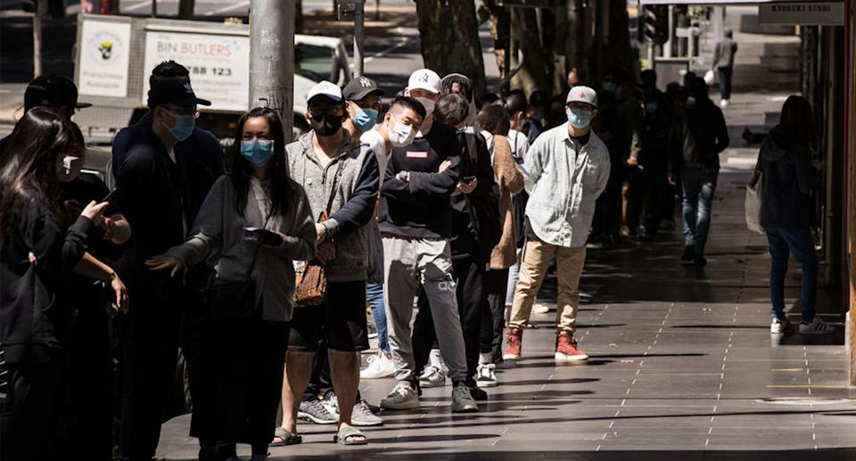 People wearing face masks stand in line.