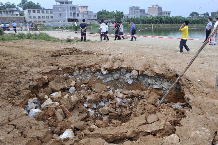 In this photo released by China's Xinhua News Agency, villagers walk past a sinkhole in Tanluo Village of Nanning City, south China's Guangxi Zhuang Autonomous Region, Saturday, June 2, 2012. More than 800 villagers have been evacuated after land sank in the province Friday, which is known for its karst topography. (AP Photo/Xinhua, Zhou Hua)