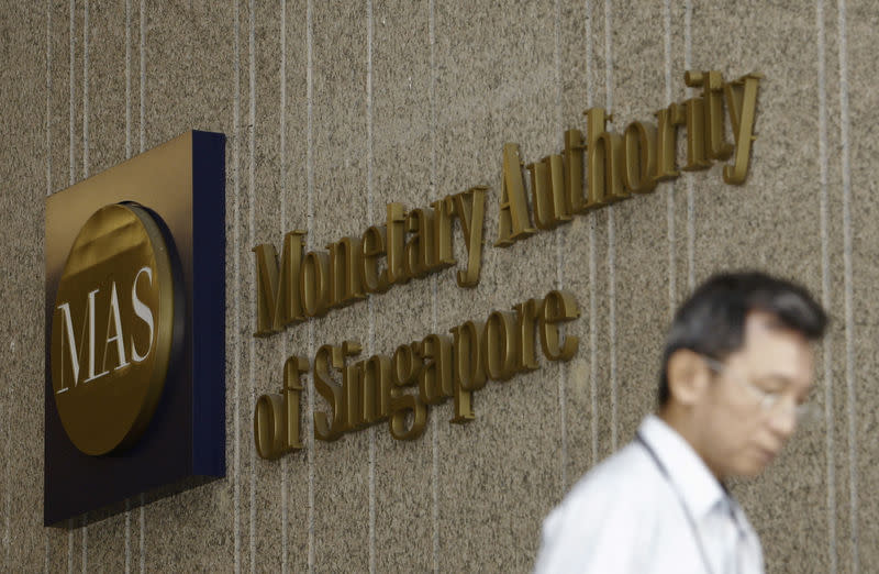 A man leaves the premises of the Monetary Authority of Singapore in the central business district of Singapore